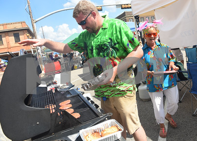 Jarrod Clayburn and Penny Smith cook hamburgers at the Lakeland House Assisted Living booth at the Uncle Fletch Davis Hamburger Festival on the courthouse square in downtown Athens Sept. 26, 2015. Athens claims that Uncle Fletch Davis invented the hamburger and shared his invention at the 1904 St. Louis World's Fair.   (Sarah A. Miller/Tyler Morning Telegraph)