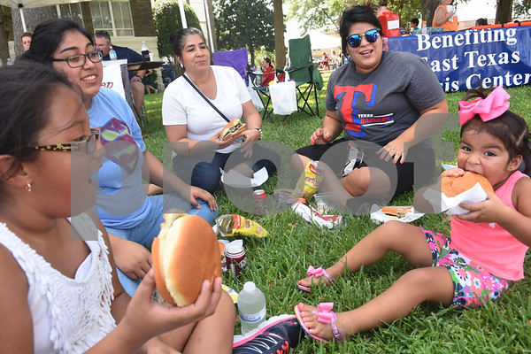 Camila Sorto, Karla Pinedo, Margarita Zavala, Fabiola Pinedo and Maggie Pacheco, 3, eat a hamburger lunch at the Uncle Fletch Davis Hamburger Festival on the courthouse square in downtown Athens Sept. 26, 2015. Athens claims that Uncle Fletch Davis invented the hamburger and shared his invention at the 1904 St. Louis World's Fair.   (Sarah A. Miller/Tyler Morning Telegraph)