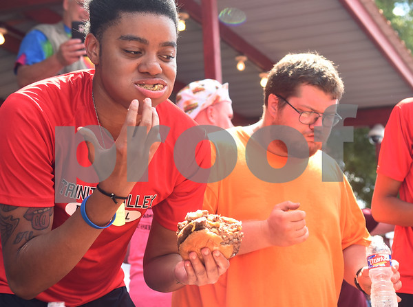 Trinity Valley Community College student Ashley Murray attempts to eat five McDonald's Double Quarter Pounders in a hamburger eating contest during the Uncle Fletch Davis Hamburger Festival on the courthouse square in downtown Athens Sept. 26, 2015. Athens claims that Uncle Fletch Davis invented the hamburger and shared his invention at the 1904 St. Louis World's Fair.   (Sarah A. Miller/Tyler Morning Telegraph)