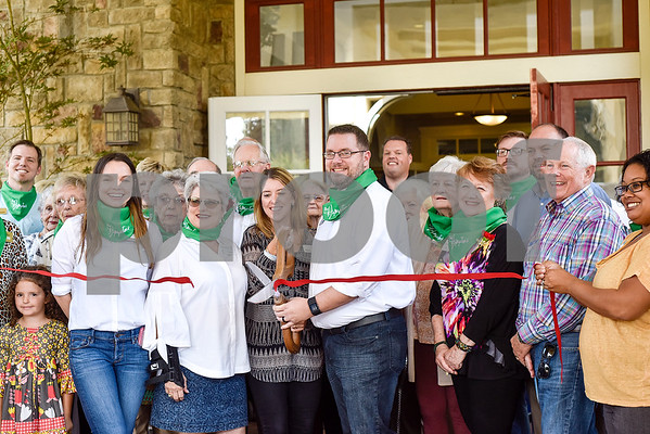 """People pose for a ribbon cutting photo during an open house event at The Hamptons in Tyler, Texas, on Thursday, Sept. 28, 2017. The event's theme was """"Around the World"""" and featured food and dessert from various countries. Attendees could also tour the newly-renovated facilities. (Chelsea Purgahn/Tyler Morning Telegraph)"""