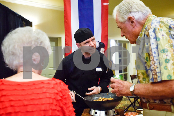 """DeWayne Grimes talks with guests about the food he is serving during an open house event at The Hamptons in Tyler, Texas, on Thursday, Sept. 28, 2017. The event's theme was """"Around the World"""" and featured food and dessert from various countries. Attendees could also tour the newly-renovated facilities. (Chelsea Purgahn/Tyler Morning Telegraph)"""