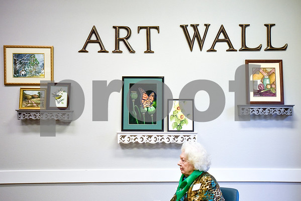 """Laree Hall sits by the Art Wall during an open house event at The Hamptons in Tyler, Texas, on Thursday, Sept. 28, 2017. The event's theme was """"Around the World"""" and featured food and dessert from various countries. Attendees could also tour the newly-renovated facilities. (Chelsea Purgahn/Tyler Morning Telegraph)"""