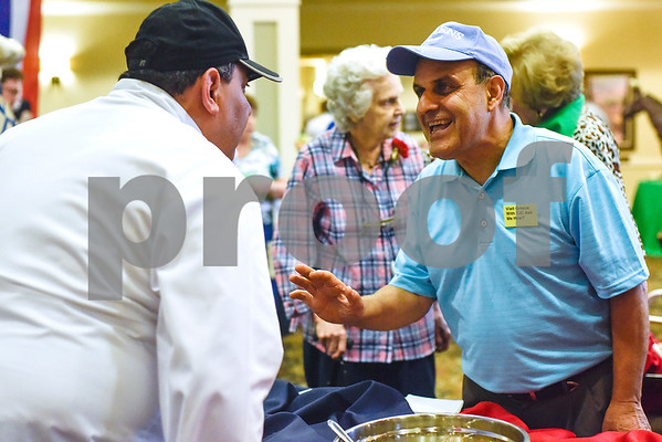 """Dr. Manoucher R. Khosrowshahi chats with a chef during an open house event at The Hamptons in Tyler, Texas, on Thursday, Sept. 28, 2017. The event's theme was """"Around the World"""" and featured food and dessert from various countries. Attendees could also tour the newly-renovated facilities. (Chelsea Purgahn/Tyler Morning Telegraph)"""