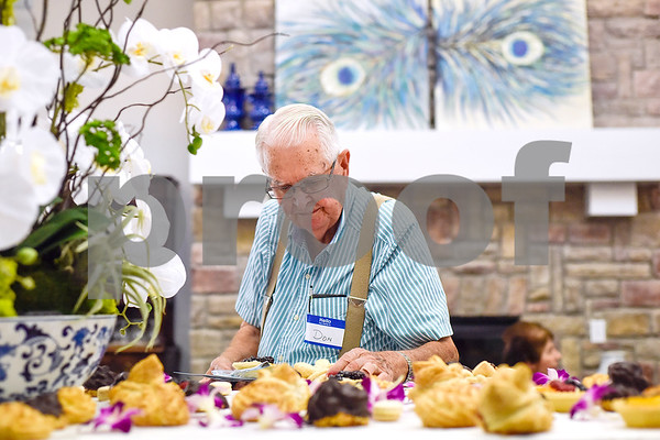 "Don Britton picks out a dessert during an open house event at The Hamptons in Tyler, Texas, on Thursday, Sept. 28, 2017. The event's theme was ""Around the World"" and featured food and dessert from various countries. Attendees could also tour the newly-renovated facilities. (Chelsea Purgahn/Tyler Morning Telegraph)"