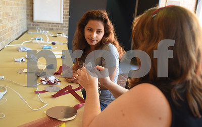 Hogg Middle School eight grader Laraina Flores is assisted by Youth Services Librarian Linda Gray during a homecoming mum making workshop held at the Tyler Public Library Saturday Sept. 3, 2016. An additional homecoming mum workshop will be held at the library on Sept. 17.   (Sarah A. Miller/Tyler Morning Telegraph)