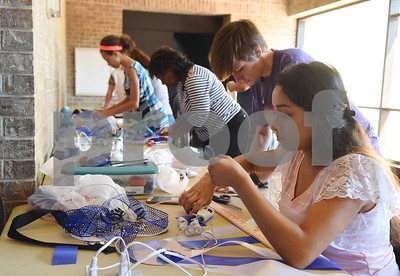 John Tyler High School junior Amy Peralata, right, folds pieces of ribbon to create a homecoming mum during a mum making workshop held at the Tyler Public Library Saturday Sept. 3, 2016. An additional homecoming mum workshop will be held at the library on Sept. 17.   (Sarah A. Miller/Tyler Morning Telegraph)
