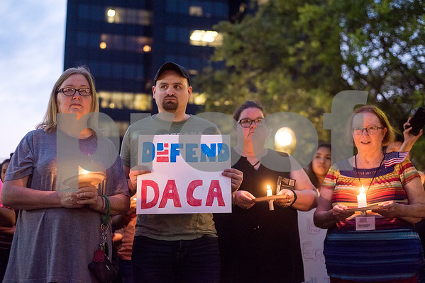 Martha Waggonner, Walker Waggonner, Katie Powell and Gail McGlothin stand in silence holding candles and signs during a silent vigil in honor of Deferred Action for Childhood Arrivals (DACA) at T.B. Butler Fountain Plaza in Tyler, Texas, on Tuesday, Sept. 5, 2017. Nearly 500 people attended the vigil on the day that the Trump administration announced that they would phase out the program. (Chelsea Purgahn/Tyler Morning Telegraph)