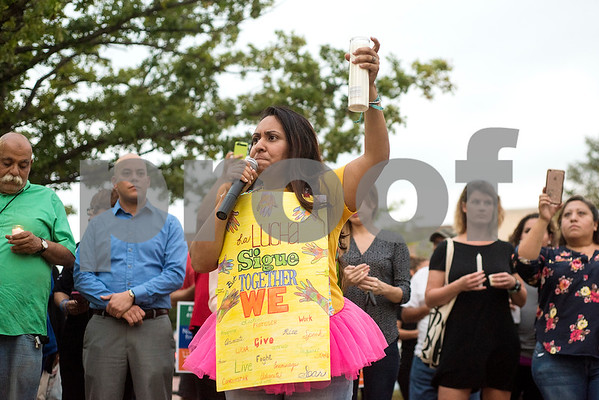 Dalila Reynoso, program administrator for Justice for our Neighbors, pauses as she holds up a candle during a silent vigil in honor of Deferred Action for Childhood Arrivals (DACA) at T.B. Butler Fountain Plaza in Tyler, Texas, on Tuesday, Sept. 5, 2017. Nearly 500 people attended the vigil on the day that the Trump administration announced that they would phase out the program. (Chelsea Purgahn/Tyler Morning Telegraph)