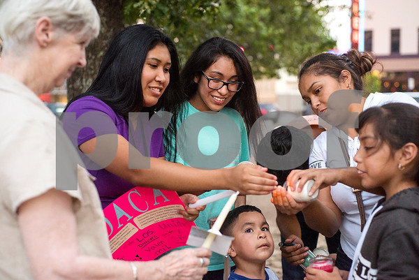 People help one another light their candles as the wind blows during a silent vigil in honor of Deferred Action for Childhood Arrivals (DACA) at T.B. Butler Fountain Plaza in Tyler, Texas, on Tuesday, Sept. 5, 2017. Nearly 500 people attended the vigil on the day that the Trump administration announced that they would phase out the program. (Chelsea Purgahn/Tyler Morning Telegraph)