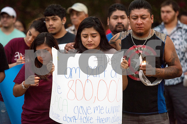 Robert E. Lee student Karina Fraga, a DACA recipient, closes her eyes in prayer as she holds a sign during a silent vigil in honor of Deferred Action for Childhood Arrivals (DACA) at T.B. Butler Fountain Plaza in Tyler, Texas, on Tuesday, Sept. 5, 2017. Nearly 500 people attended the vigil on the day that the Trump administration announced that they would phase out the program. (Chelsea Purgahn/Tyler Morning Telegraph)