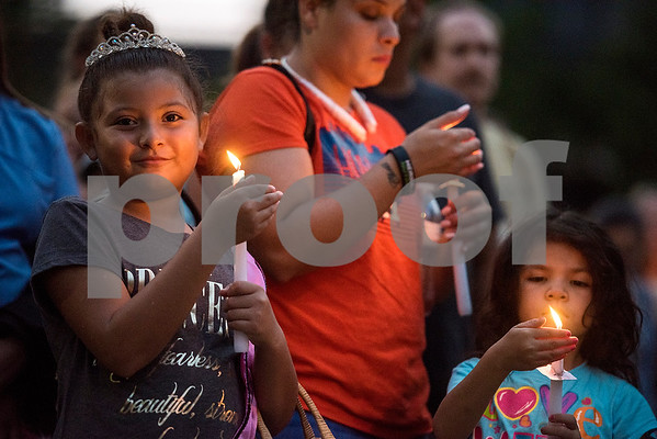 Gisselle Guerra, 8, looks towards the camera as she, Katherine Guerra and Kamilla Guerra, 5, hold candles during a silent vigil in honor of Deferred Action for Childhood Arrivals (DACA) at T.B. Butler Fountain Plaza in Tyler, Texas, on Tuesday, Sept. 5, 2017. Nearly 500 people attended the vigil on the day that the Trump administration announced that they would phase out the program. (Chelsea Purgahn/Tyler Morning Telegraph)