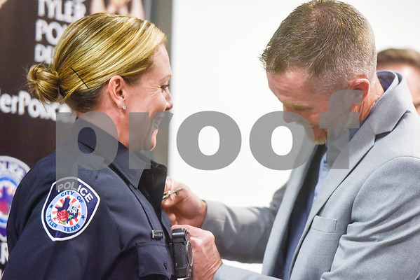 Amber Thomas is pinned with her new badge by her husband at the Tyler Police Department in Tyler, Texas, on Tuesday, Sept. 4, 2018. Seven new police recruits were sworn in and received their badges during the ceremony. (Chelsea Purgahn/Tyler Morning Telegraph)