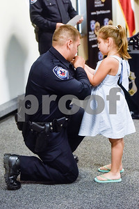 Rusty Adair is pinned with his new badge by his daughter at the Tyler Police Department in Tyler, Texas, on Tuesday, Sept. 4, 2018. Seven new police recruits were sworn in and received their badges during the ceremony. (Chelsea Purgahn/Tyler Morning Telegraph)