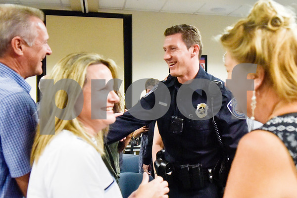 George Edwards III laughs with others after being sworn in at the Tyler Police Department in Tyler, Texas, on Tuesday, Sept. 4, 2018. Seven new police recruits were sworn in and received their badges during the ceremony. (Chelsea Purgahn/Tyler Morning Telegraph)