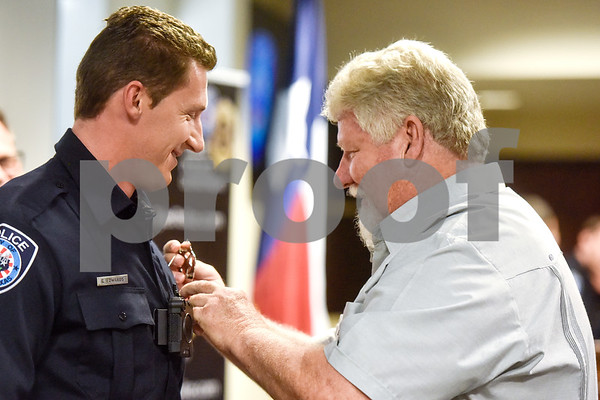 George Edwards III is pinned with his new badge by his father at the Tyler Police Department in Tyler, Texas, on Tuesday, Sept. 4, 2018. Seven new police recruits were sworn in and received their badges during the ceremony. (Chelsea Purgahn/Tyler Morning Telegraph)