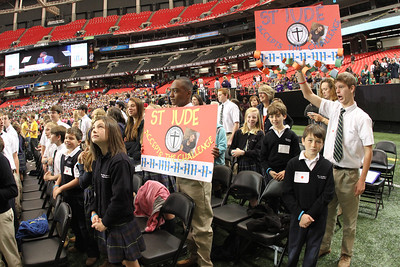 St. Jude the Apostle School eighth-graders Chandler Parks, center, and Jack Gillett hold signs as the students watch the paper chains unfurl and rise to heights above the stage on both sides. Through various acts of compassion and kindness displayed by Rachel's Challenge participants, they estimate that 10 miles of chains were collected and brought to The Georgia Dome.