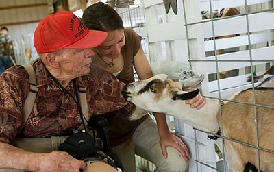 Record-Eagle/Douglas Tesner<br /> Jack Green, 83, and his friend and caretaker Ashley Rubritius pet a goat looking for attention at the Northwestern Michigan Fair's 4-H displays. The fair, which ended Saturday, celebrated its 100th anniversary this year.