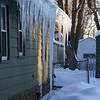 Icicles hanigng from a neighbouring house, one of which reaches the ground