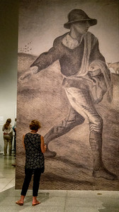 Exhibit visitor with replica of van Gogh's Sower