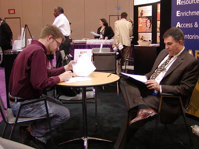 "ASHG 2006: FASEB/MARC booth in exhibit hall. Joe Tringali critiques a resume for a graduate student in the ""Career Corner."""