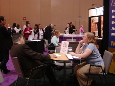 """ASHG 2006: FASEB/MARC booth in exhibit hall. Joe Tringali critiques a resume for a graduate student in the """"Career Corner."""""""