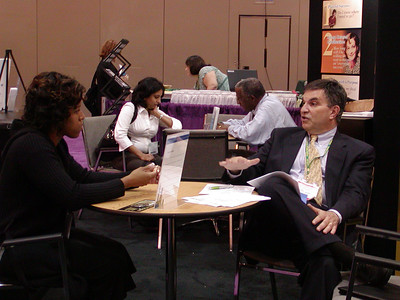 "ASHG 2006: FASEB/MARC booth in exhibit hall. Joe Tringali meets with students in the ""Career Corner."""