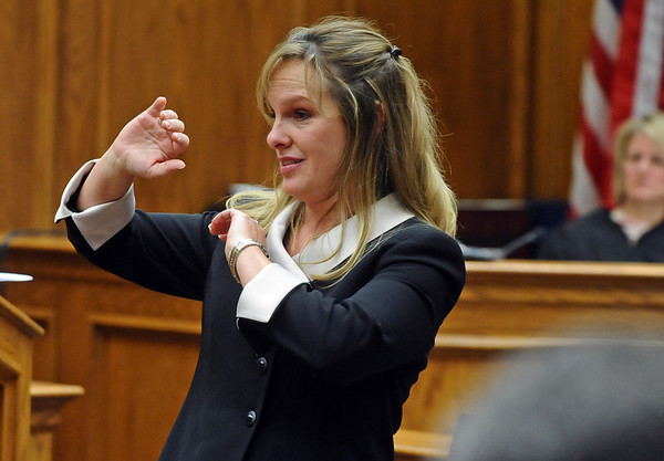 Prosecutor Katharina Booth demonstrates the possible defensive posture of William Andrews when he was shot, which would explain the severe damage to his right forearm, during her closing argument in the trial of Joseph Abeyta.<br /> Photo by Marty Caivano/Camera/Oct. 23, 2009/