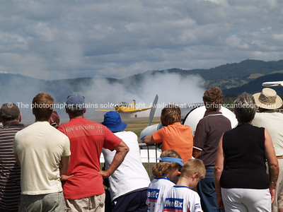 Tauranga Airshow, 2008. New Zealand. Crowd watches a burnout. Tauranga is New Zealands 5th largest city and offers a wonderfull variety of scenic and cultural experiences. ALSO SEE; http://www.blurb.com/b/3811392-tauranga