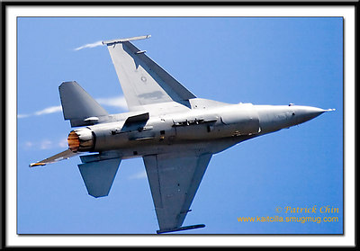 F-16 passing the crowd flying side way.