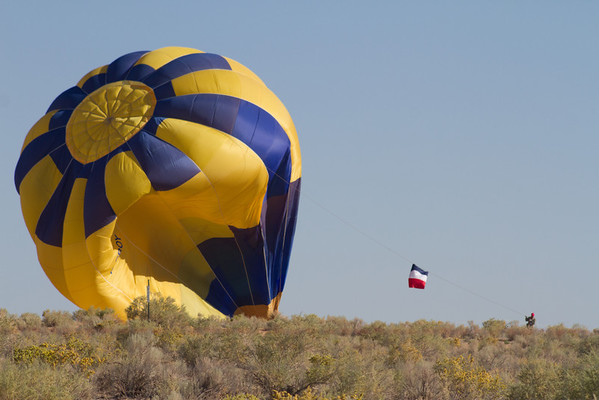 Pilot Ettore Cadel hanging onto the crown line to bring the balloon down.