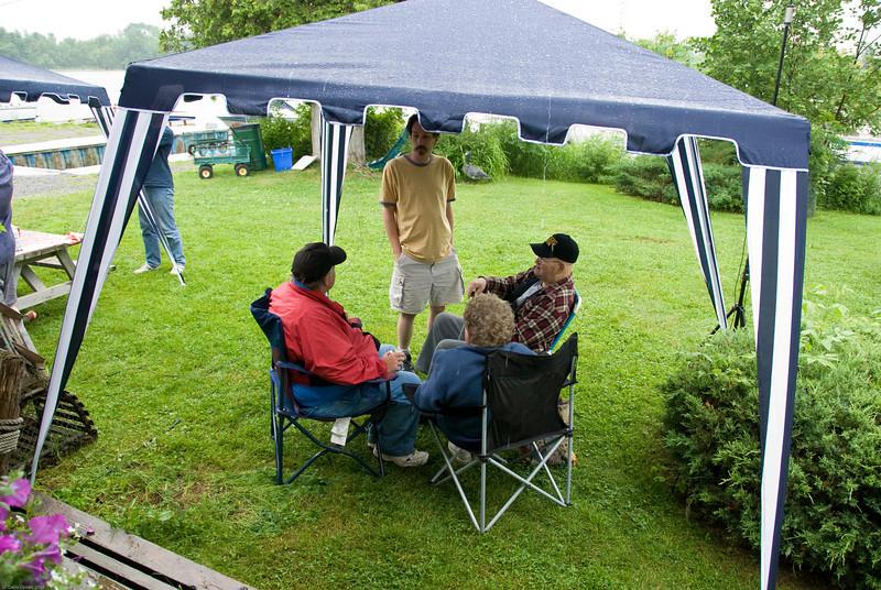 Mike (VA3MPM, standing), Steve (VE3SKP), and Gerry (VE3GFG) get some respite from the often torrential rain.