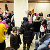 "Children line up with their parents to take a photo with the ""3 Kings,"" (back left) former Cleghorn Neighborhood Center youth director Jason Jordan, 24, of Ayer, past CNC board president Nathan Bilotta of Fitchburg, and State Rep. Stephen DiNatale, Thursday night during the Cleghorn Neighborhood Center's annual 3 Kings event at the Saint Joseph Church in Fitchburg.<br /> SENTINEL & ENTERPRISE / BRETT CRAWFORD"