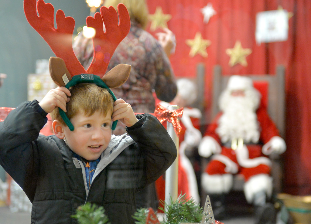 Justin Sheely | The Sheridan Press<br /> Three-year-old Jax Zabroski plays with a head ornament as he waits in line for pictures with Santa during the annual Christmas Stroll Friday in downtown Sheridan.