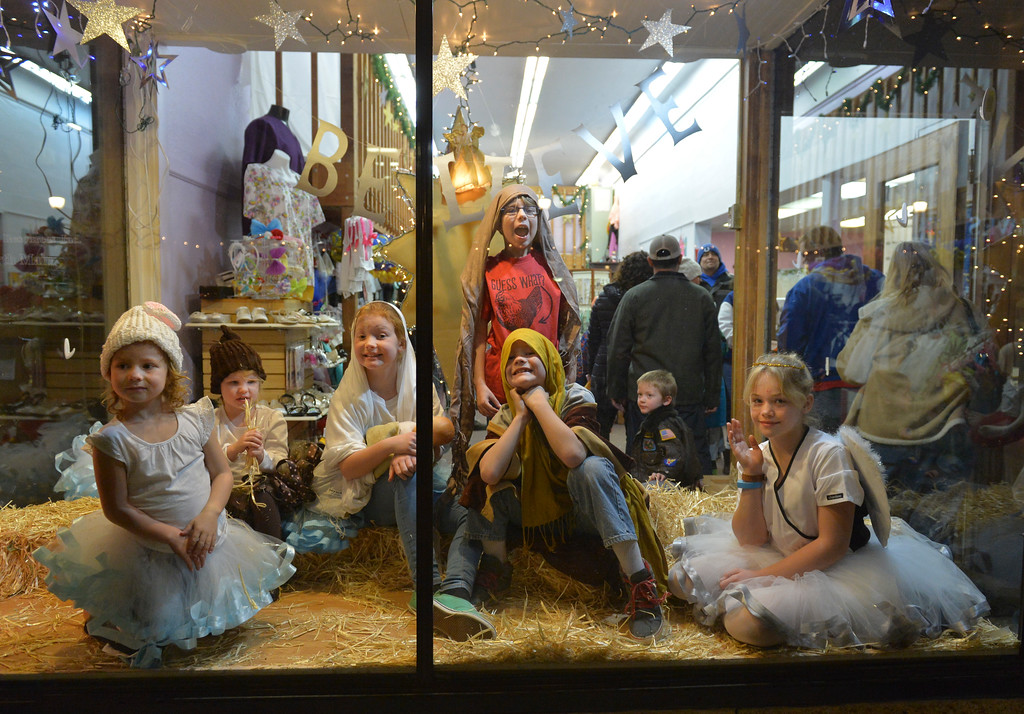 Justin Sheely | The Sheridan Press<br /> Nativity characters, from left, Hailey Hungerford, Piper Brown, Aliyah Hungerford, Xavier Brown, Tommy Hungerford and Brylee Brehmer wave as people passing by the window at Once Upon a Story during the annual Christmas Stroll Friday in downtown Sheridan.