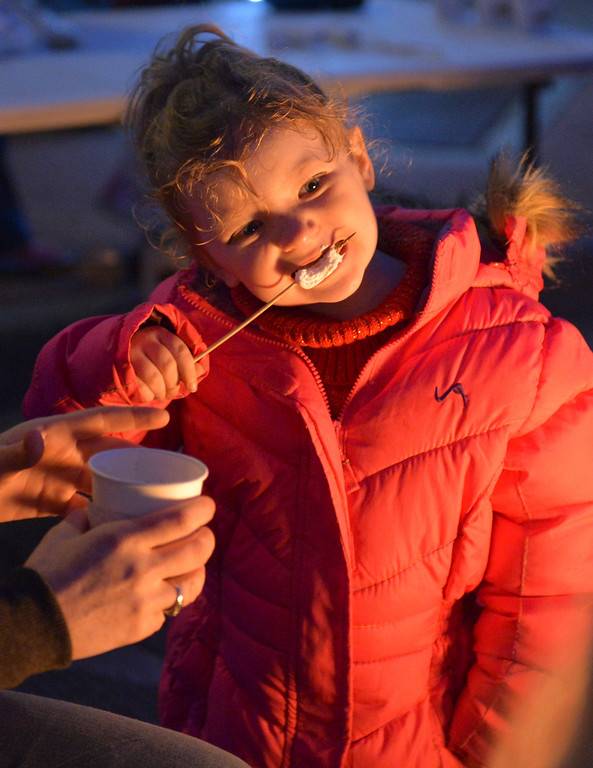 Justin Sheely | The Sheridan Press<br /> Three-year-old September Knox takes a bite from her roasted marshmallow during the annual Christmas Stroll Friday in downtown Sheridan.