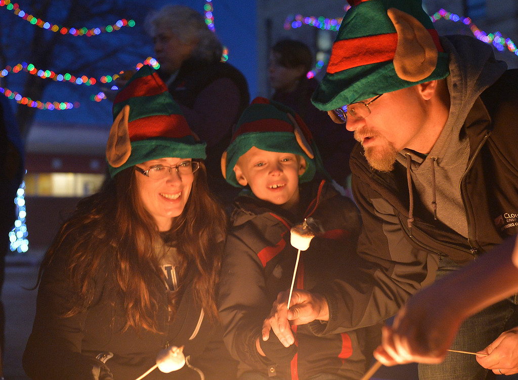 Justin Sheely | The Sheridan Press<br /> Jodeen Showers, left, and Dylan Showers, 6, react as David Showers blows out a burning marshmallow during the annual Christmas Stroll Friday in downtown Sheridan.