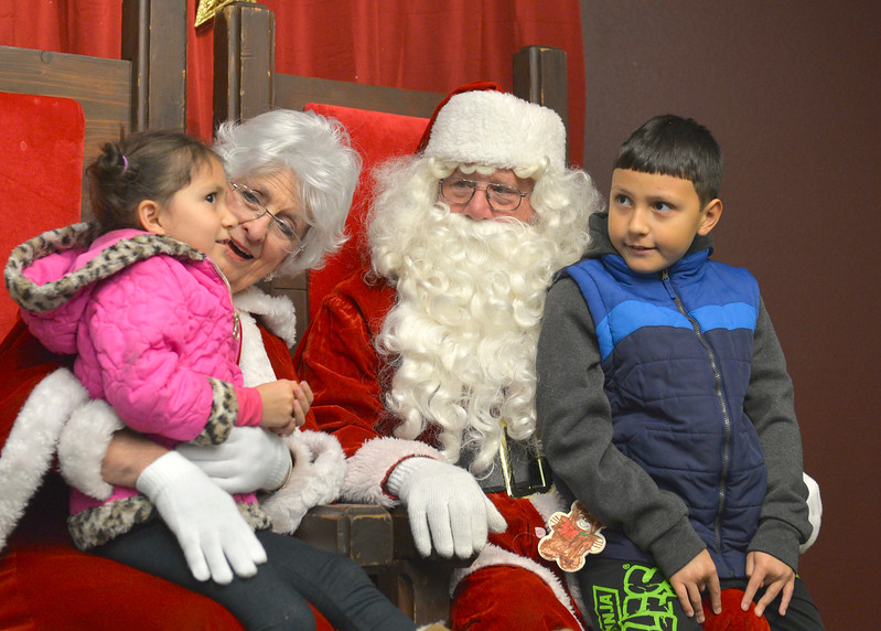 Justin Sheely | The Sheridan Press<br /> Five-year-old Julie Skarin, left, and Michael Skarin, 10, visit Mr. and Mrs. Santa Claus during the annual Christmas Stroll Friday in downtown Sheridan.