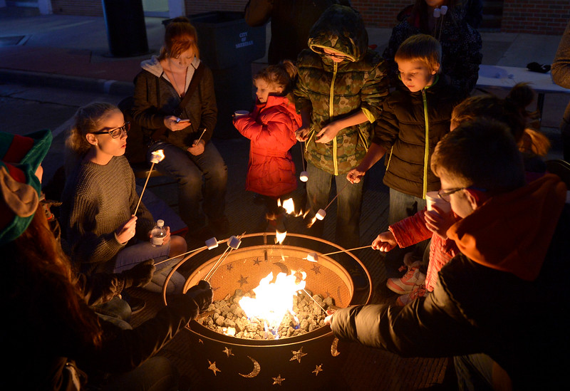 Justin Sheely | The Sheridan Press<br /> People roast marshmallows over a fire during the annual Christmas Stroll Friday in downtown Sheridan.