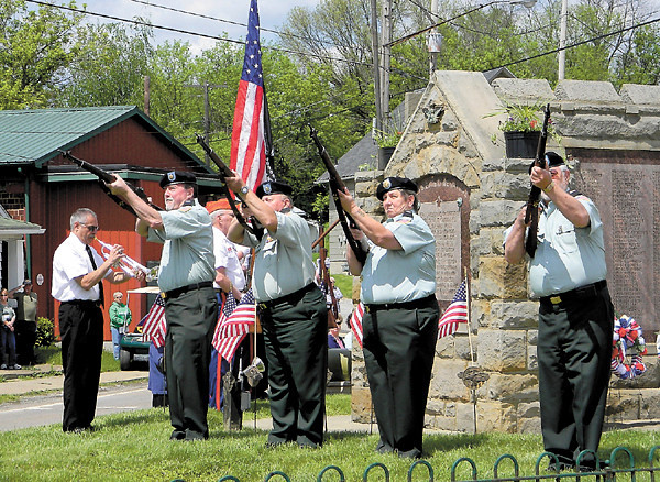The New Castle Honor Guard provides a rifle salute as 'Taps' is played to end the ceremony. — Dan Irwin