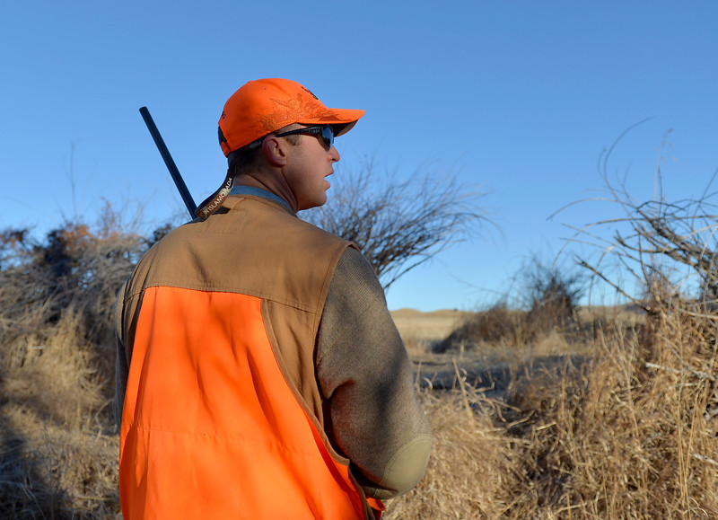 Justin Sheely | The Sheridan Press<br /> Chad Franklin walks downhill from his daughter as their dog runs ahead during the 5th-annual Kids' Pheasant Hunt Saturday at Fort Phil Kearny State Historic Site. The event provides an opportunity for youth to learn and practice safe hunting skills with experienced adults.