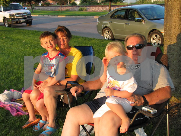 Kim Myers with Dorian Groff on her lap, and Mark White with Daphne Groff on his lap wait for the fireworks to begin near the Marian Home.