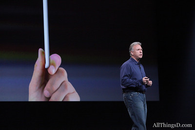 Schiller walks in front of a promotional image touting the iPad mini's thinness.