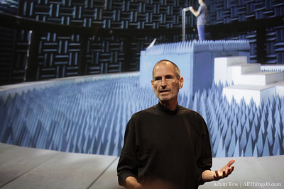 Steve Jobs behind a photo of Apple's iPhone testing facility.