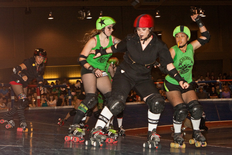 """The girls with the star on the helmet are the scorers. Her goal is to pass or """"lap"""" everybody else. The opposing team tries to prevent this while her team tries to help by blocking for her and giving her centrifugal sling assists."""