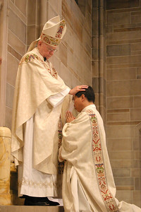 Archbishop John F. Donoghue lays hands on ordination candidate Cyril Soo-Gil Chae. The action signifies conferral of God's Holy Spirit.  (Page 4, July 1, 2004 issue)