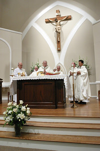 Archbishop John F. Donoghue, center, is joined on the altar by (l-r) Deacon Don Kelsey, Father Bill Williams, parochial vicar at St. John Neumann Church, Lilburn, Father Richard Tibbetts, pastor of St. Theresa Church, Douglasville, Father Patrick Kingery, pastor of Holy Cross Church, Atlanta, and Christ Our King and Savior pastor Father Fernando Molina-Restrepo. Also in the background are Father Carlo DiNatale-Taras, left, and Father Luis S. Osorio from the Diocese of Charlotte, N.C.