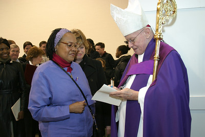 Following the Rite of Election and Call to Continuing Conversion, Glenda Ham, a candidate from the Shrine of the Immaculate Conception, Atlanta, waits as Archbishop John F. Donoghue autographs her program.   (Page 4, March 11, 2004 issue)