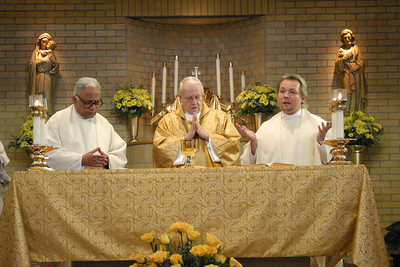 Father Joseph Mendes, MSFS, Visitation Monastery chaplain, left, and Father Peter Jandaczek, MS, parochial vicar at St. Oliver Plunkett Church, Snellville, right, join Archbishop John F. Donoghue at the altar during the Liturgy of the Eucharist of the June 27 Mass commemoraing the 50th anniversary of the monastery's foundation in the Archdiocese of Atlanta.    (Page 14, July 22, 2004 issue)