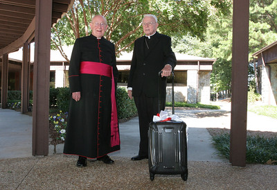 Archbishop-emeritus John F. Donoghue, right, has lived at the All Saints Church rectory with Msgr. R. Donald Kiernan, left, pastor of All Saints, for five years. Archbishop Donoghue holds a piece of luggage the Knights of Columbus gave him as a parting gift for his move to St. George Village.