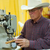 """Keith Lockie, of Jordan, Mont., tries out a """"Cowboy"""" leather sewing machine Friday at the Rock Mountain Leather Trade Show in the Convention Center at the Holiday Inn."""
